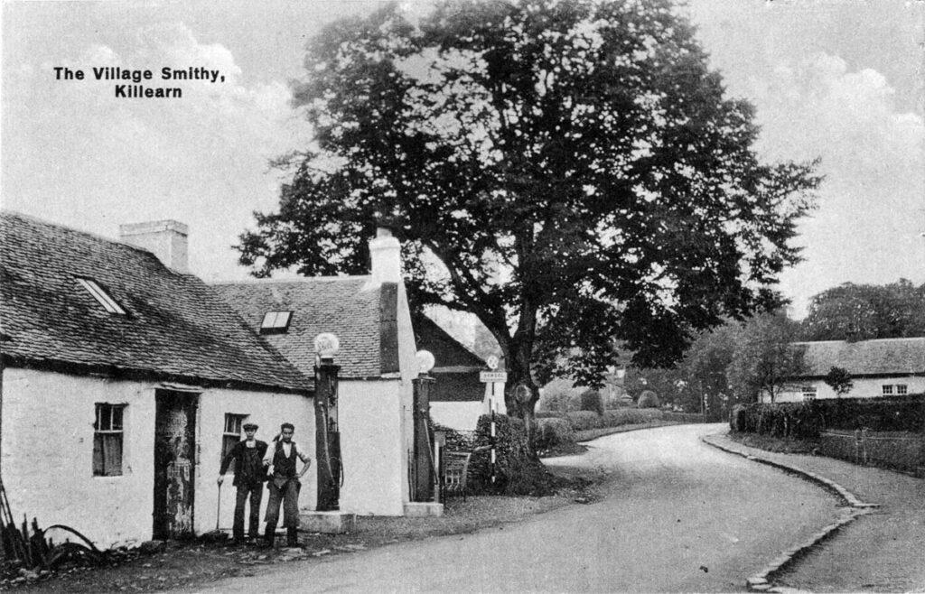 Two men stand outside the village smithy in Killearn alongside an otherwise empty road