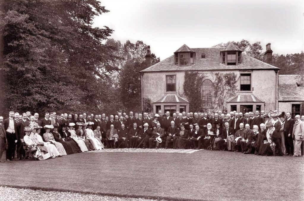 A large group of people sit and stand for a formal photograph in front of a large mansion in the early 20th-Century