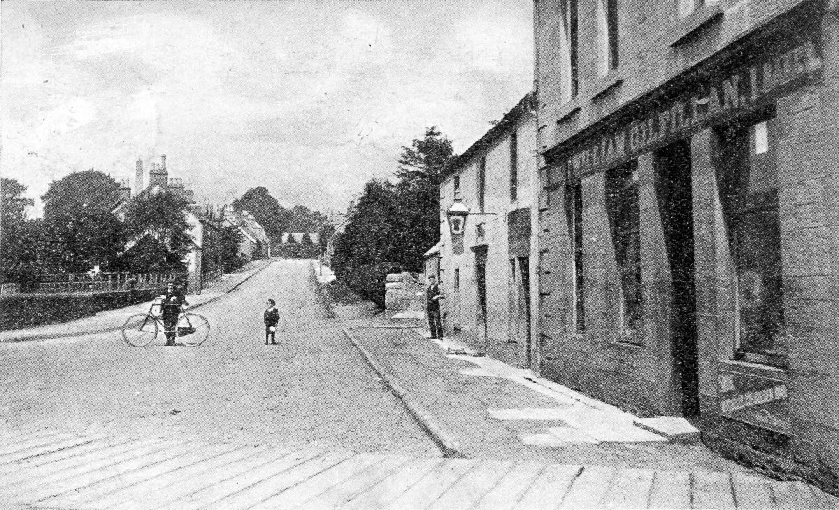 A boy and a man holding a bicycle stand in an otherwise empty JMain Street in Killearn, next to another man standing outside the Wheat Sheaf Pub