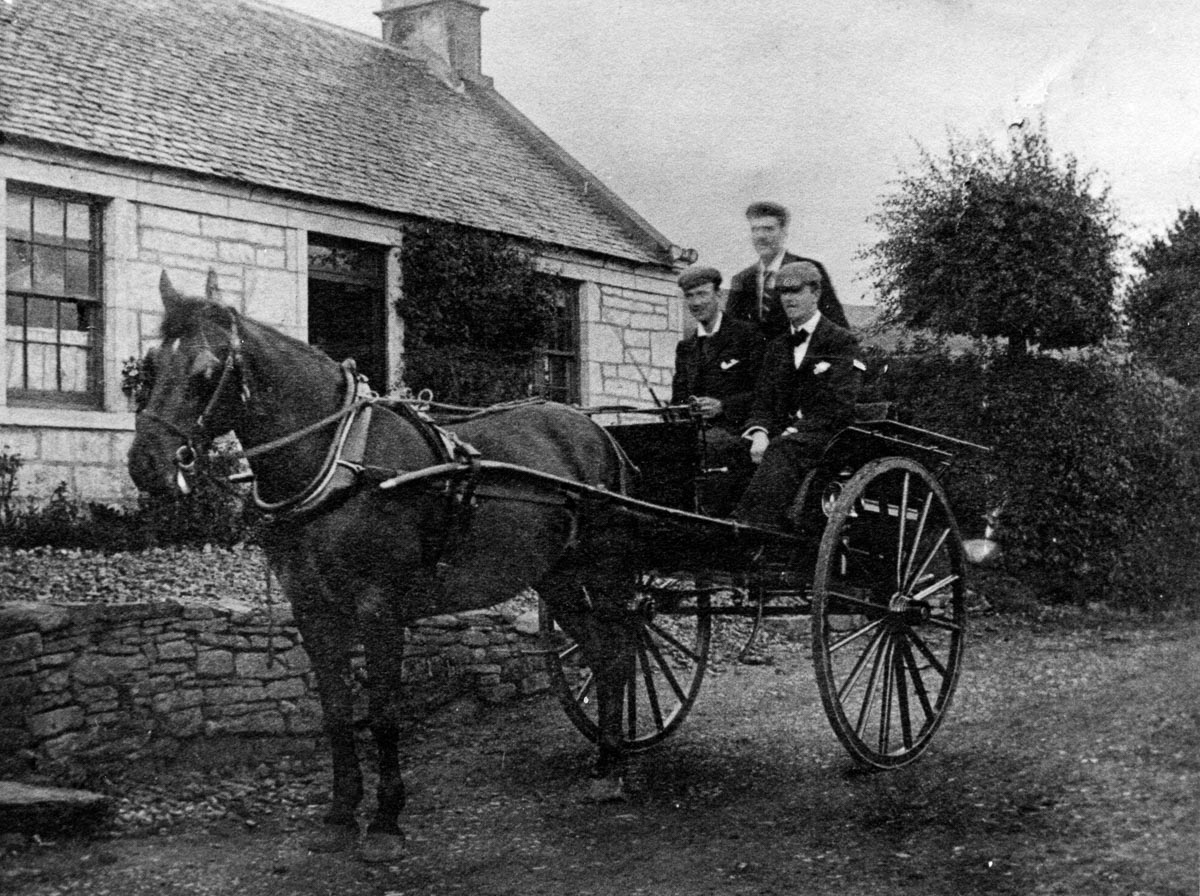 Black and white photo of three men sitting on a horse and cart outside a building in the early 20th-century