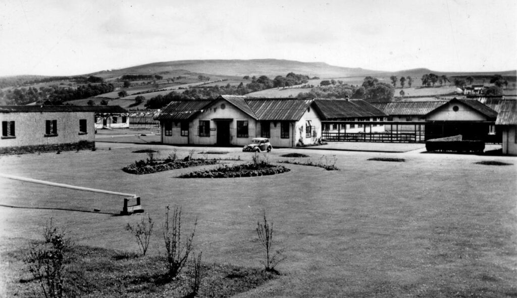 A black and white photo looking over a large lawn towards a number of separate buildings that made Killearn Hospital