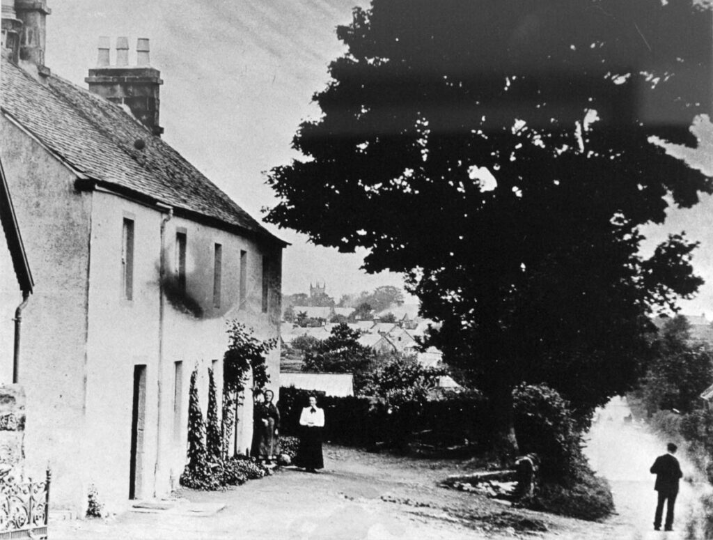 Black and white photo of several people standing outside Killearn Kirkhouse in the early 20th-century