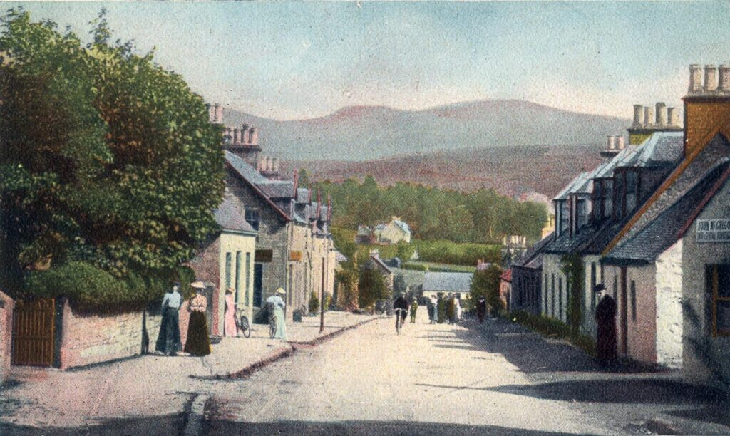 A scan of a colour postcard featuring a view of people milling in Killearn Main Street, and the Campsie hills in the distance
