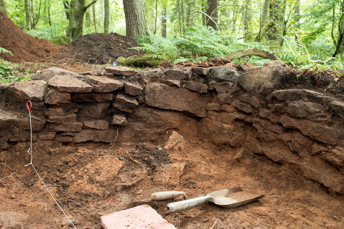 Partial remains of a building found in woodland along with tools used to excavate it.