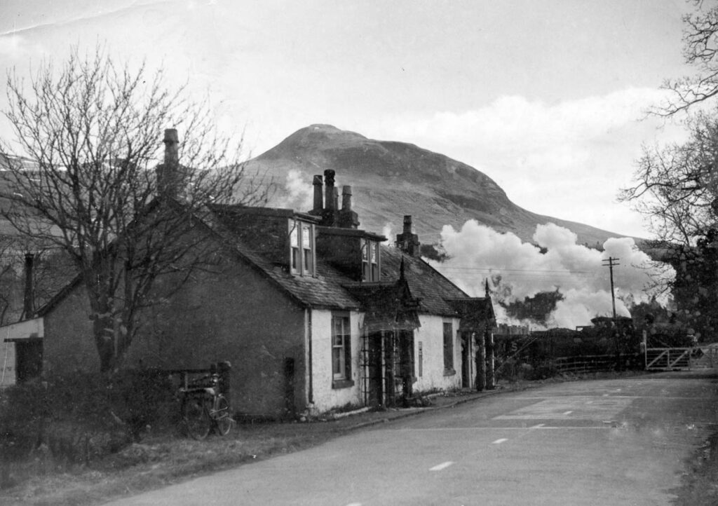 A partially hidden steam train billows out steam as it passes behind the old Post Office at Dumgoyne, with the Campsie hills in the background