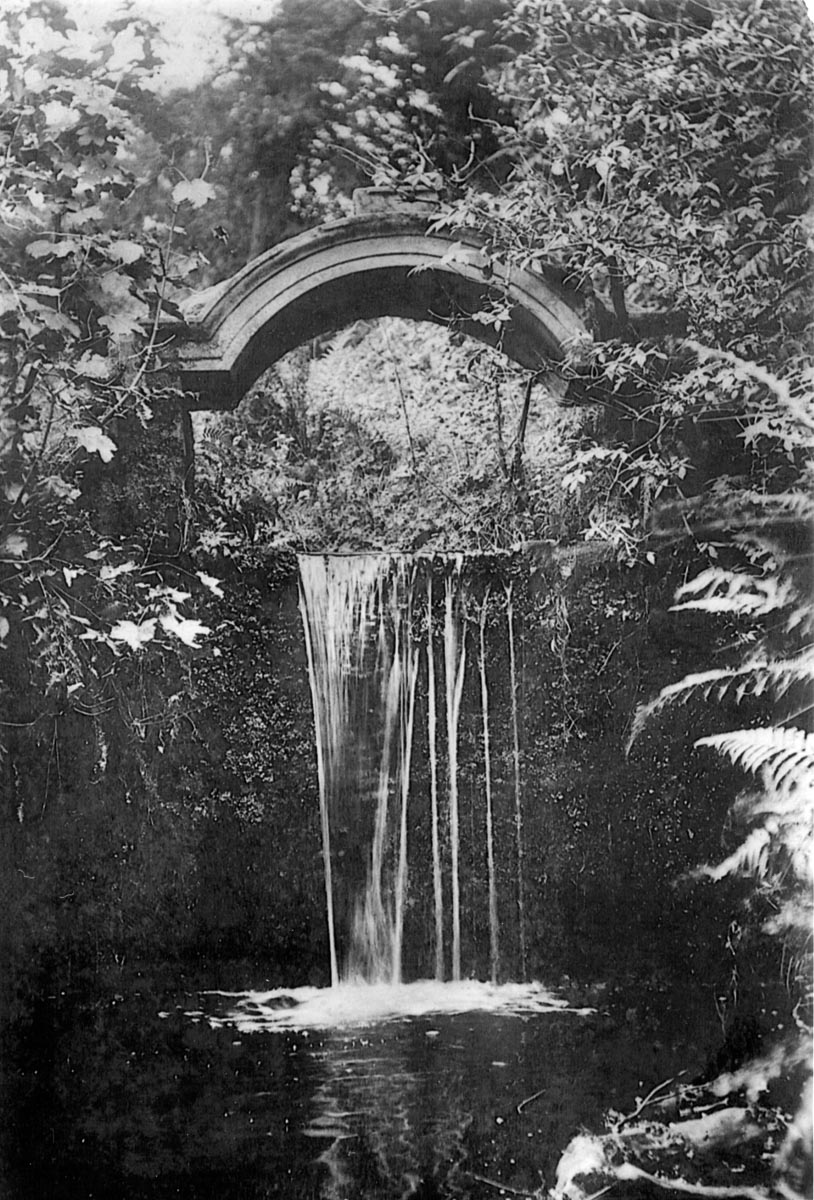 Scan of a black and white postcard, featuring a waterfall called the Ladies Linn passing below a decorative stonework arch