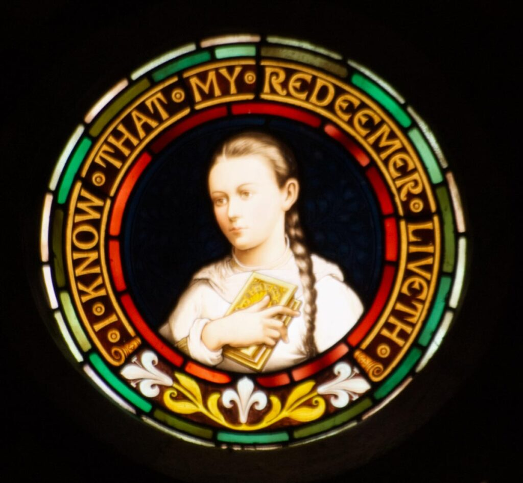Stained glass portrait of a young woman with circular border featuring text that says 'I know that my redeemer liveth'