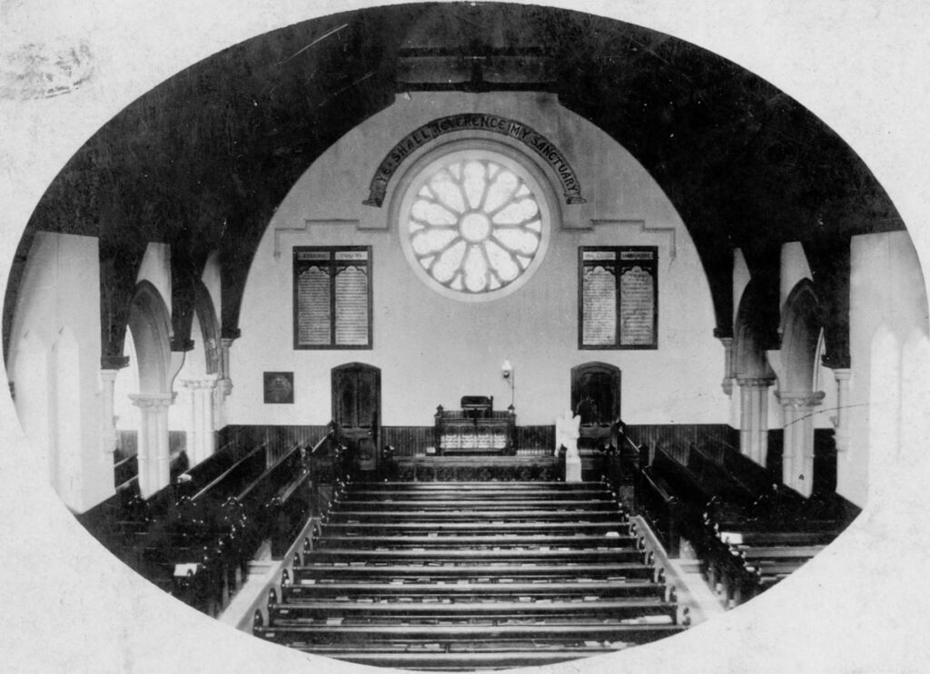 black and white picture looking over church pews towards a stained glass rose window