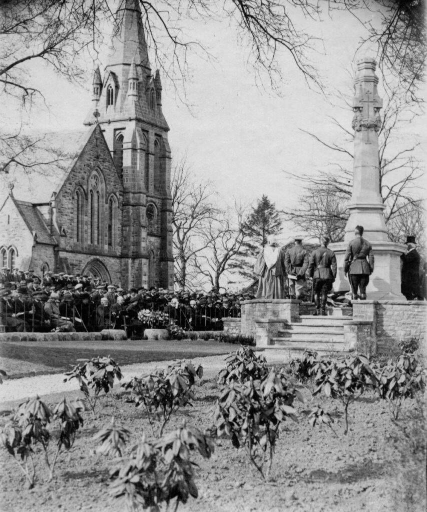 Crowd of people including soldiers in uniform, standing beside Killearn's war memorial, with the church in the background