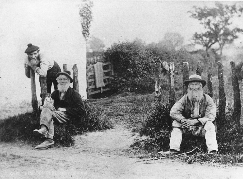 Black & white photo of three men looking at camera while resting in Killearn Village
