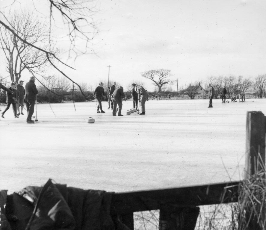 Black and white picture of a group of adults curling on a frozen pond