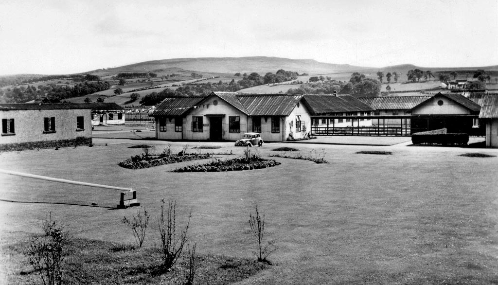 old photo of a number of single-storey barrack-style buildings. In front of them is a neat lawn area and a single parked car