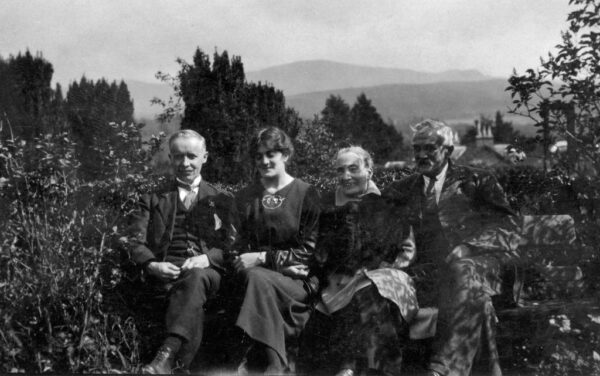 Black and white photograph of a younger man and woman sat next to an elderly couple on a bench with trees and hills in the background