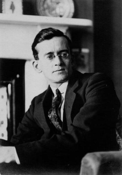 Black and white candid photo of a dapper man wearing glasses