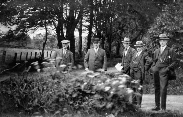Black and white picture of five men in suits standing on a country road