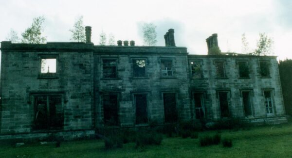 Vintage photo of a derelict stone building that is in disrepair