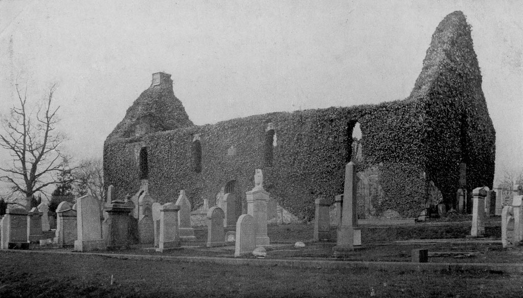 Black and white photo of abandoned church with grave stones in front