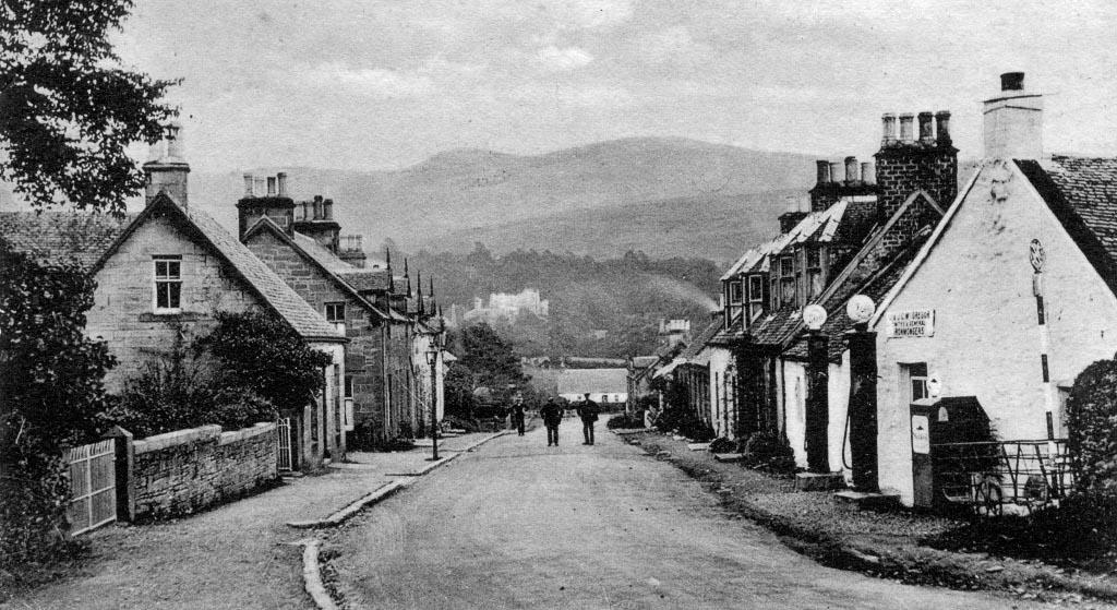black and white photo of Killearn Main Street. Men walking down road. Hills in