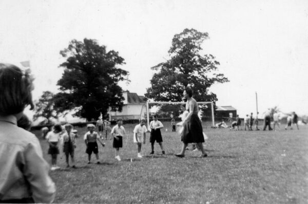 Children are lined up in a field with a football goal in the background whilst a teacher appears to be speaking to them. in the background there is another group of children exercising.