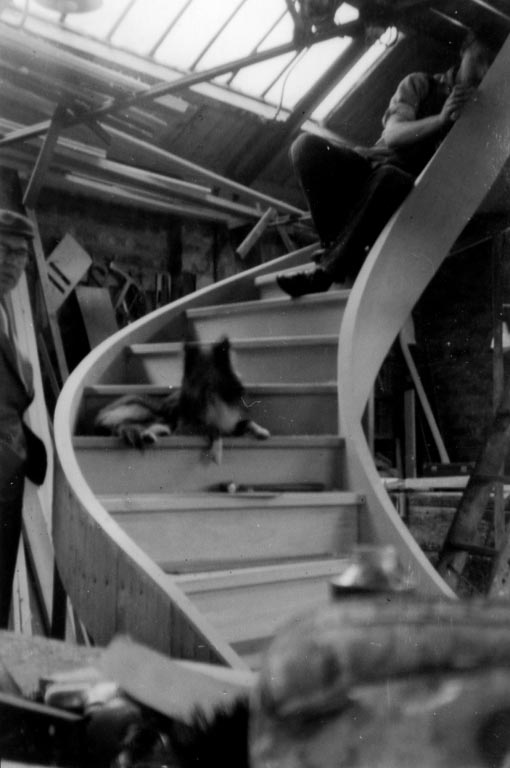 Black and white photo of a dog sat on a spiral staircase in a workshop with workmen around