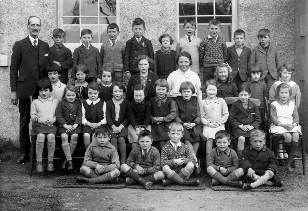 Black and white formal school picture of a class and their teacher in the 1930s