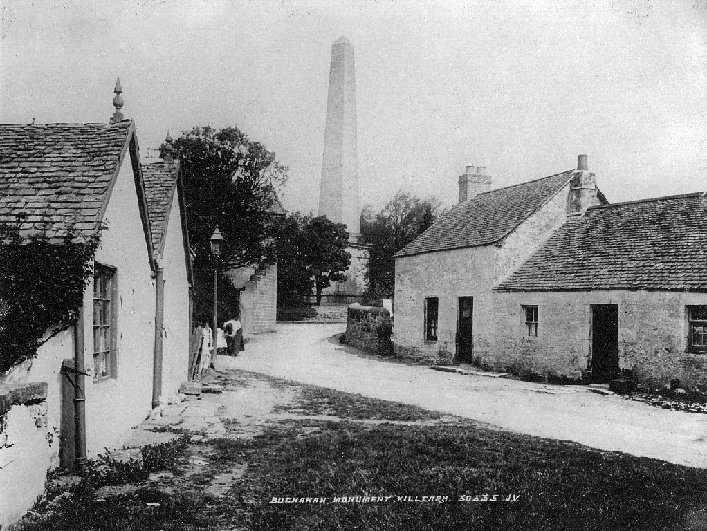 Black and white photo of a street with houses on both sides and a large monument in the background