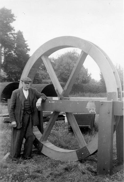 Black and white photo of a man next to a water wheel
